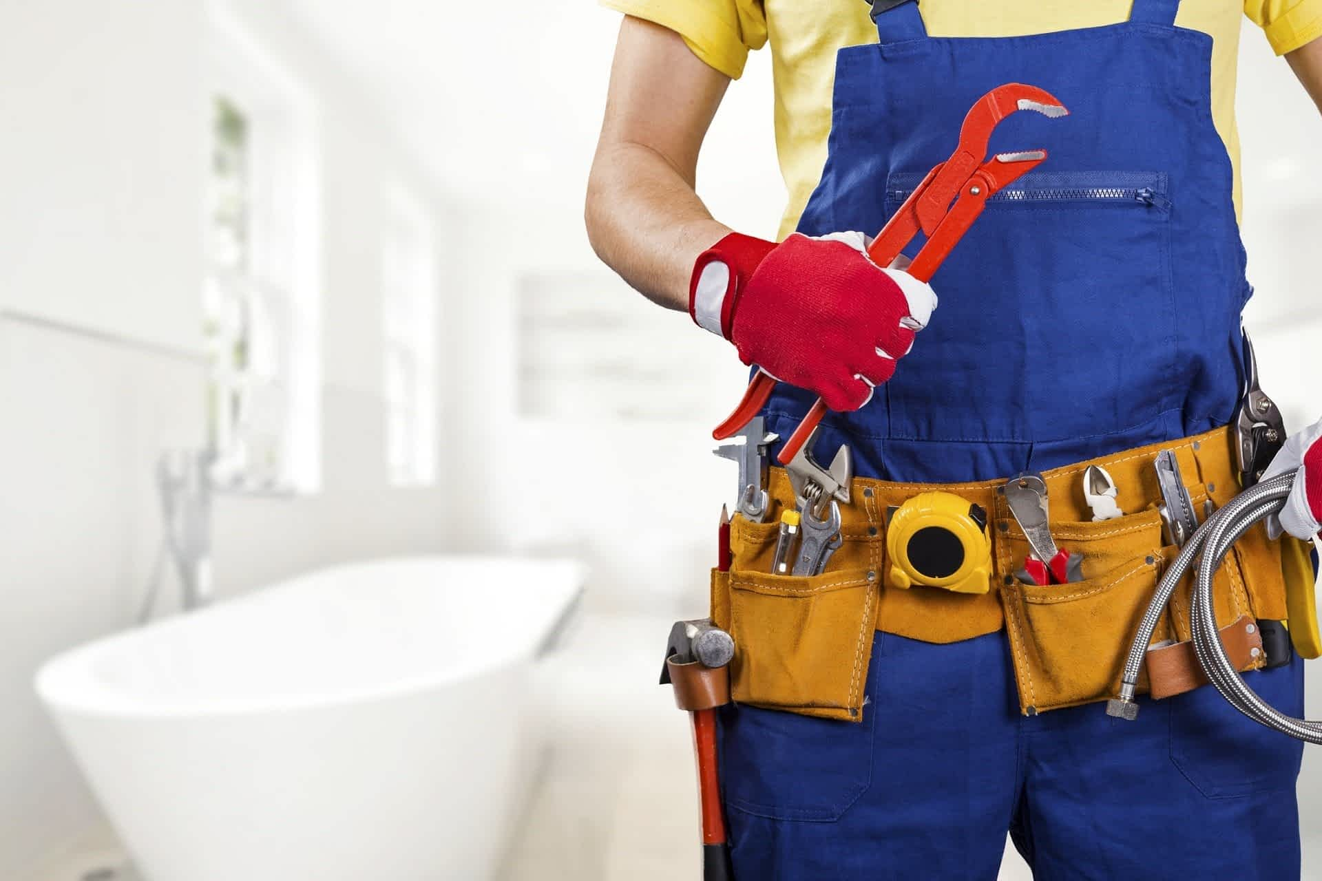 plumber with tool belt standing in bathroom